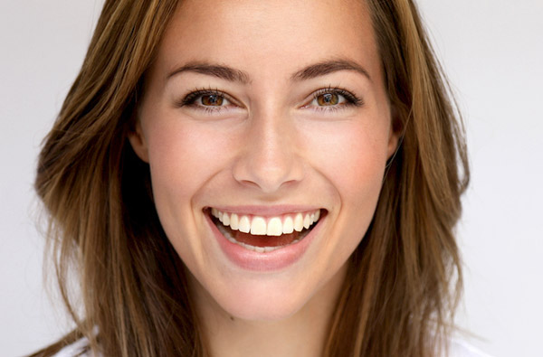 Woman smiling with white teeth after cosmetic dental services from Alexandra Garcia, DDS